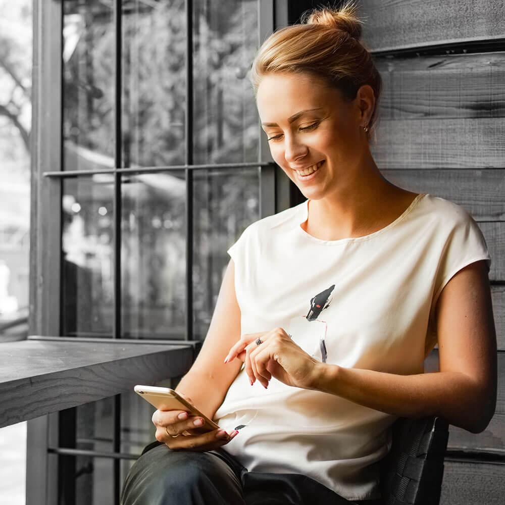 Eine Bewerberin sucht auf dem Handy nach Stellenanzeigen und Jobangeboten.