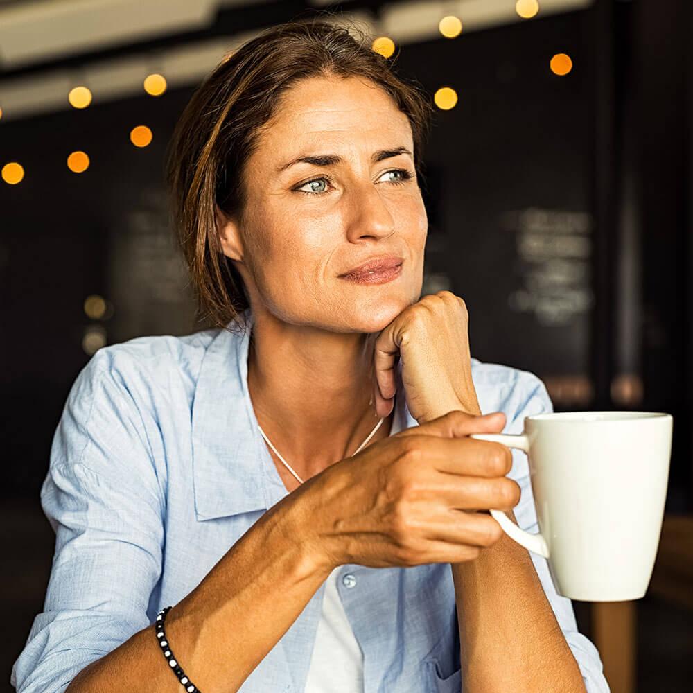 Eine Frau mit Tasse in der Hand, die über Ihre Karriere nachdenkt.