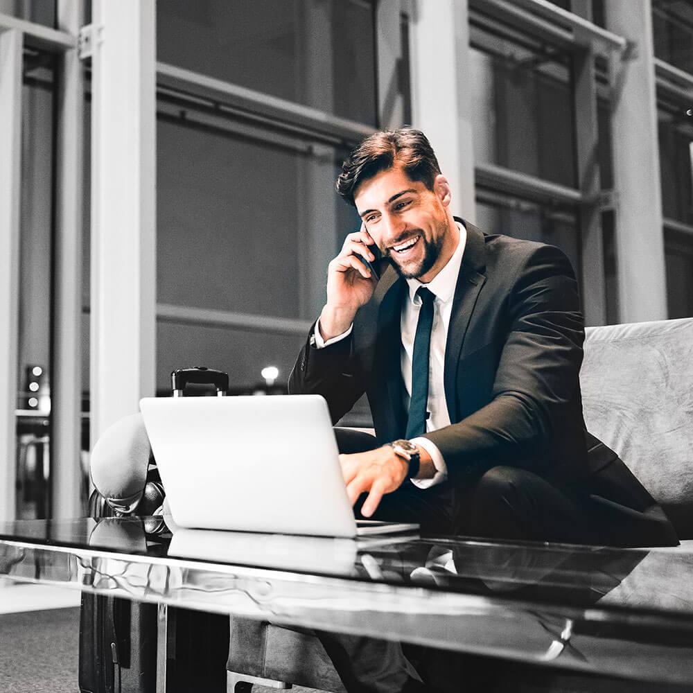 Headhunter sitzt abends im Büro, vor seinem Laptop und telefoniert am Handy.