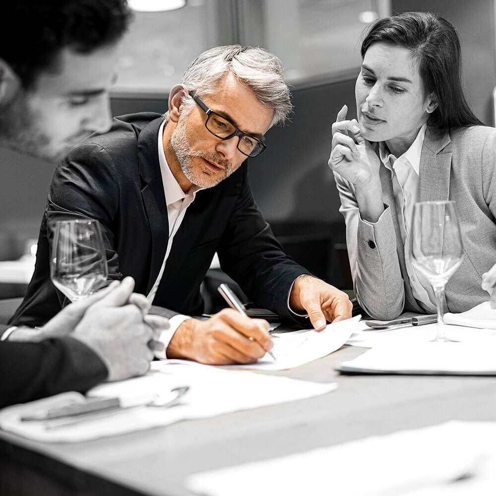 Ein Interim Manager erklärt an einem Tisch einen Prozessablauf. Ein Mann und eine Frau sehen ihm interessiert über die Schulter