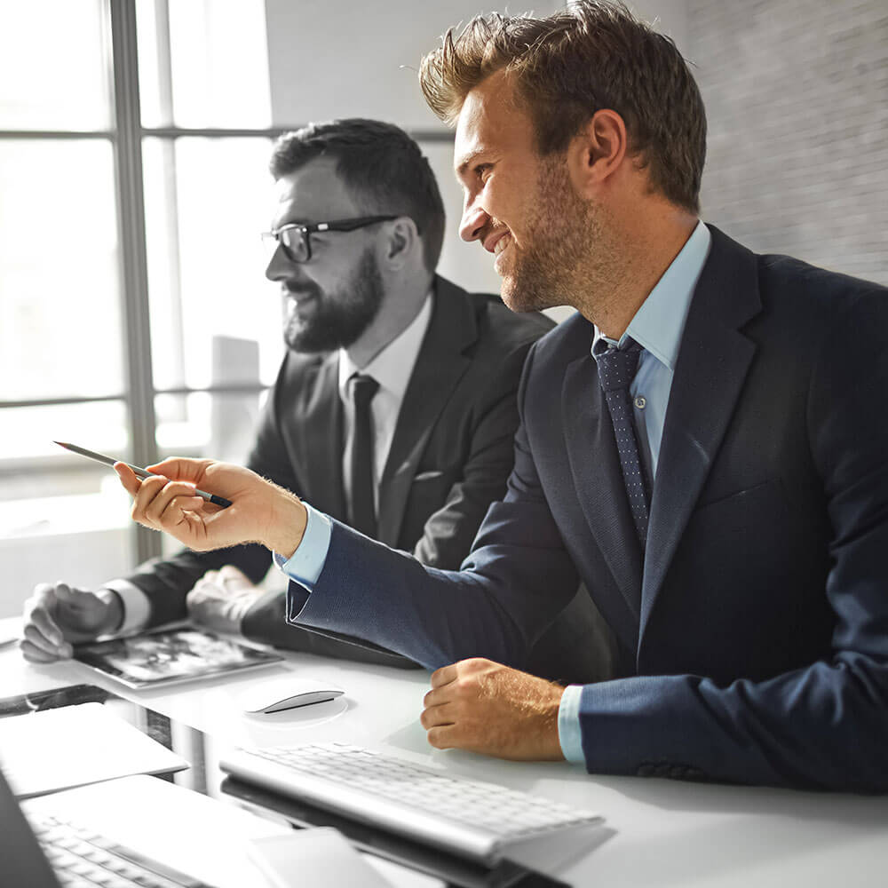 Der Interim Manager zeigt einem Angestellten etwas auf dem Bildschirm. Er deutet mit einem Stift in die Richtung.