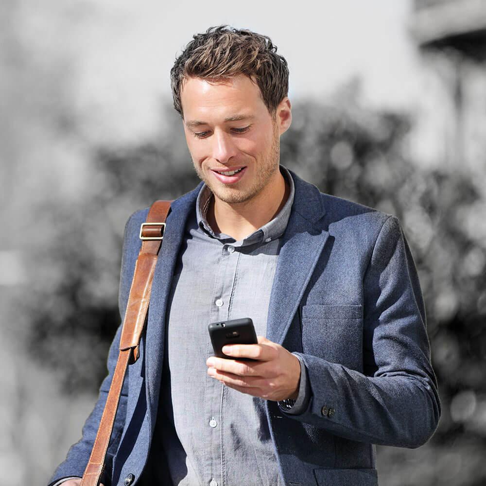 Ein junger Herr in Sacko der auf sein Handy schaut, auf dem Weg zur Karriereberatung