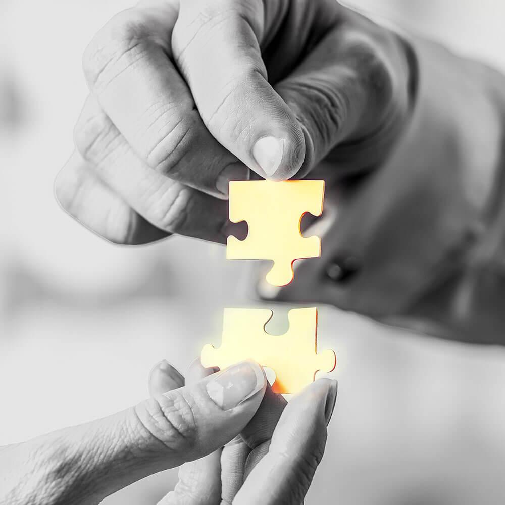 Zwei Hände in Nahaufnahme die zwei Puzzleteile zusammensetzen