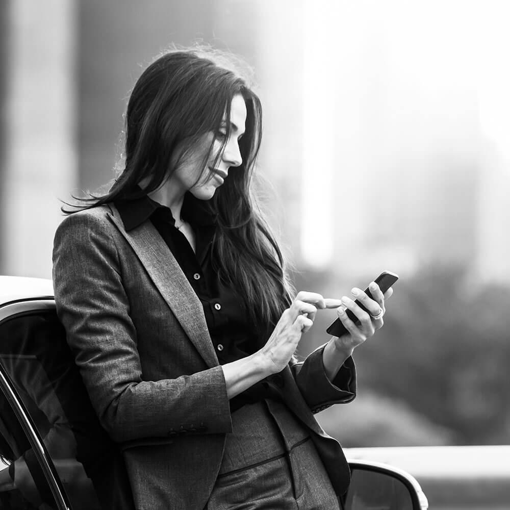 Eine Karrierefrau mittleren Alters die, nach der Karriereberatung, an ein Auto gelehnt auf ihrem Handy tippt.